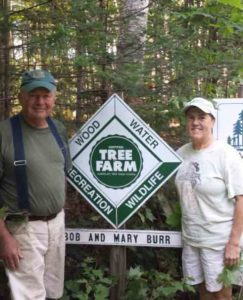 Bob & Mary Burr standing next to their tree farm sign.