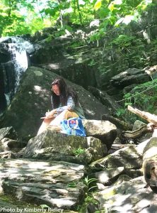 A writer sits at the base of Goodell Brook Falls.