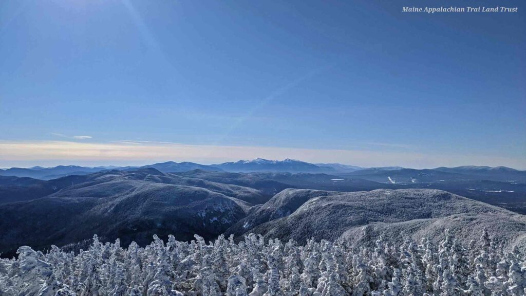 Snow-crusted trees and endless mountains are visible from the summit of Old Speck in Maine's western mountains.